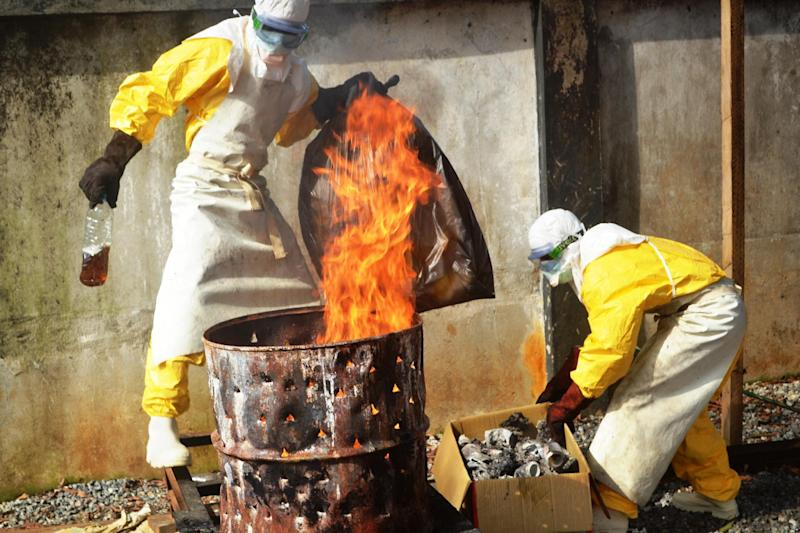 Health workers burn used protective gear at the Medecins Sans Frontieres center in Conakry on September 13, 2014 (AFP Photo/Cellou Binani)