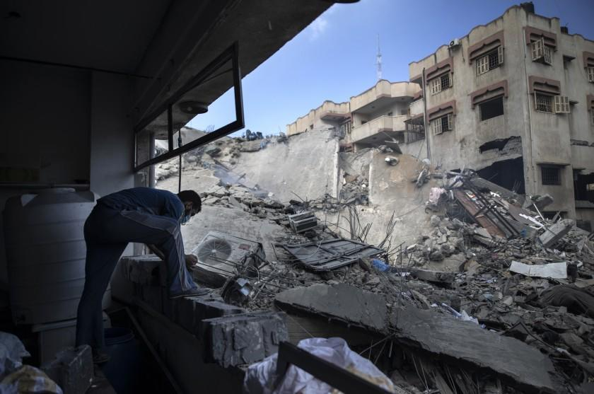 A Palestinian man inspects the damage of a six-story building which was destroyed by an early morning Israeli airstrike, in Gaza City, Tuesday, May 18, 2021. Israel carried out a wave of airstrikes on what it said were militant targets in Gaza, leveling a six-story building in downtown Gaza City, and Palestinian militants fired dozens of rockets into Israel early Tuesday, the latest in the fourth war between the two sides, now in its second week. (AP Photo/Khalil Hamra)