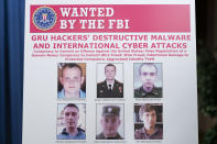 A poster showing six wanted Russian military intelligence officers is displayed before a news conference at the Department of Justice, Monday, Oct. 19, 2020, in Washington. (AP Photo/Andrew Harnik, pool)