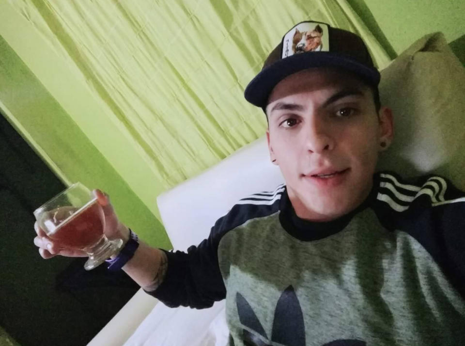 Alfredo Emilio Escobar wearing a cap and holding up a beverage.