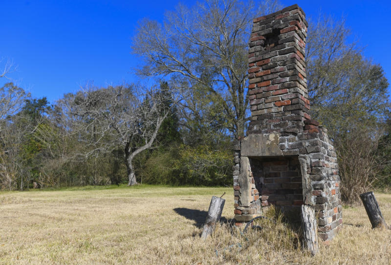FILE - In this Tuesday, Jan. 29, 2019, file photo, a chimney, the last remaining original structure from the days when survivors of the Clotilda, the last known slave ship brought into the United States, inhabited the area, stands in an abandoned lot in Africatown in Mobile, Ala. On Wednesday, May 22, 2019, authorities said that researchers have located the wreck of Clotilda. (AP Photo/Julie Bennett, File)