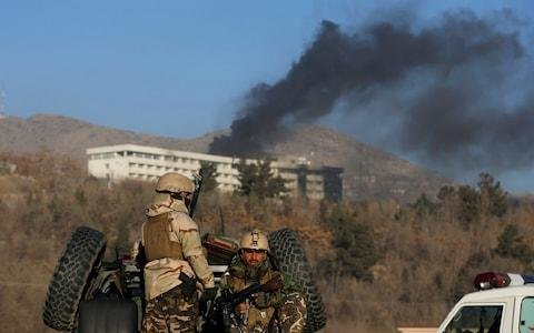 Afghan security forces keep watch as smoke rises from the Intercontinental Hotel on Sunday - Credit: OMAR SOBHANI/REUTERS