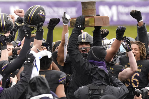 Northwestern football head coach Pat Fitzgerald celebrates with players as he holds the Land of Lincoln Trophy after Northwestern defeated Illinois 28-10 in an NCAA college football game in Evanston, Ill., Saturday, Dec. 12, 2020. (AP Photo/Nam Y. Huh)