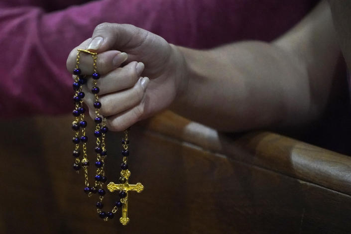 A young woman holds a rosary as she prays, late Saturday, June 26, 2021, during a prayer vigil for the victims and families of the Champlain Towers collapsed building in Surfside, Fla., at the nearby St. Joseph Catholic Church in Miami Beach, Fla. Many people were still unaccounted for two days after Thursday's fatal collapse. (AP Photo/Wilfredo Lee)