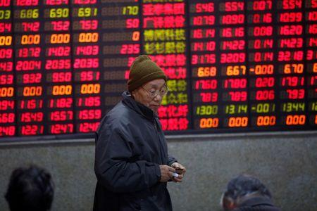 An investor walks in front of an electronic board showing stock information on the first trading day after the New Year holiday at a brokerage house in Shanghai, China, January 3, 2017.  REUTERS/Aly Song