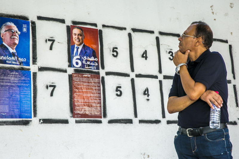 A man looks at a wall of campaign posters in Tunis, Tunisia, Monday, Sept. 2, 2019.Tunisia's 26 presidential candidates have launched their campaigns in a political climate marked by uncertainty, money laundering allegations and worries about violent extremism. (AP Photo/Hassene Dridi)
