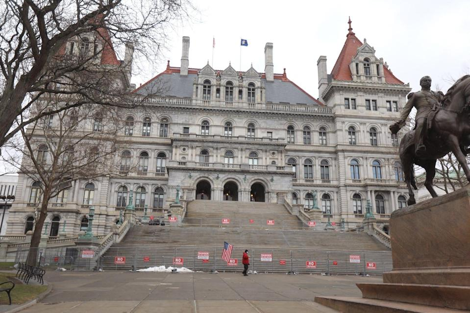 One person with a flag walks by the New York State Capitol in Albany Jan. 17, 2021.