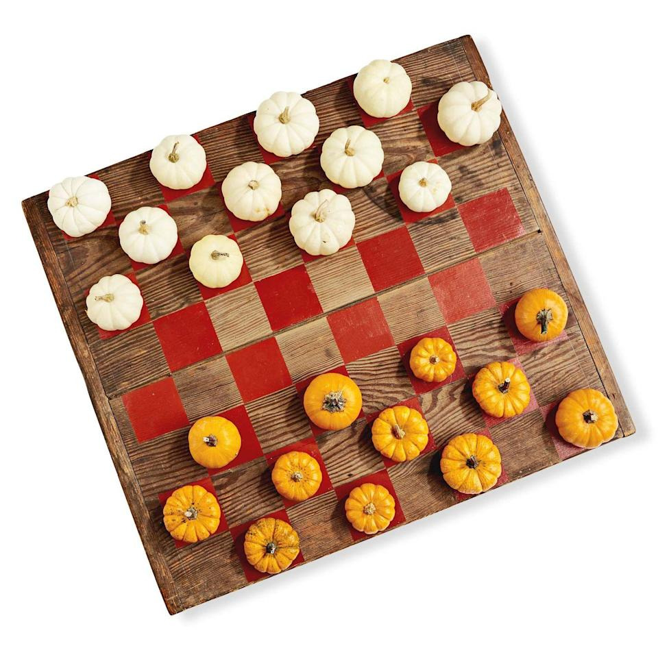 <p>Paint 32 squares on a large (roughly 30-inch) wood board with burnt orange craft paint. Use mini white and orange pumpkins as game pieces.</p>