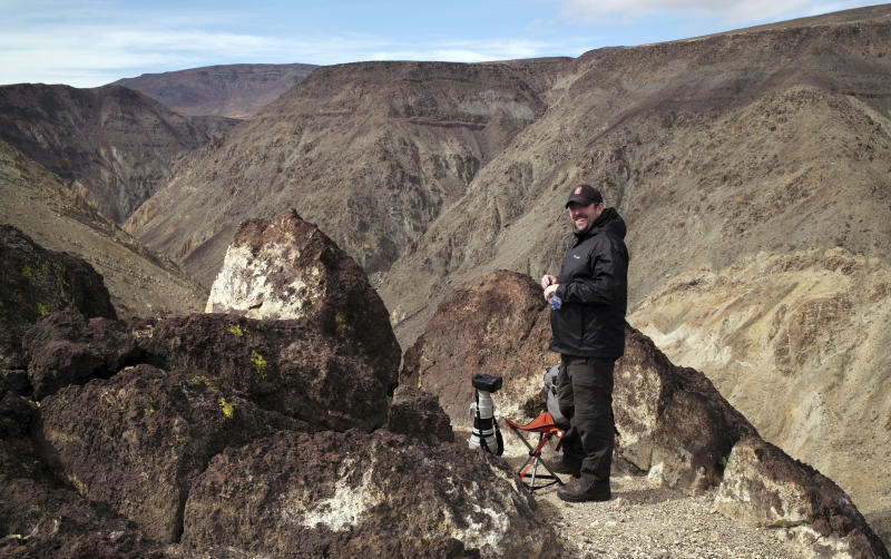 In this photo taken Feb. 28, 2017, photographer Jason O. Watson waits on a cliff overlooking the nicknamed Star Wars Canyon in Death Valley National Park, Calif. Military jets roaring over national parks have long drawn complaints from hikers and campers. But in California's Death Valley, the low-flying combat aircraft skillfully zipping between the craggy landscape has become a popular attraction in the 3.3 million acre park in the Mojave Desert, 260 miles east of Los Angeles.(AP Photo/Ben Margot)