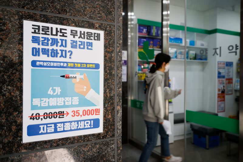 A woman walks past a poster encouraging people to get an influenza vaccine in Seoul