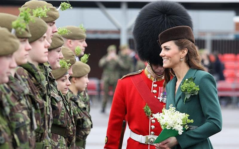 The Duchess of Cambridge presents shamrocks to Irish Guards during a St Patrick's Day parade at Aldershot Barracks - Credit: Getty