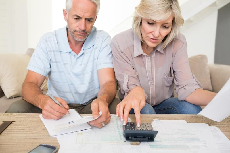 Mature couple looking over finances and a calculator together.