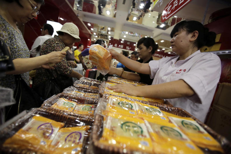 In this Sept. 12, 2013 photo, a vender, right, sells mooncakes to a customer, left, at a shop in Shanghai, China. The mooncake, a traditional pastry that's given during the Chinese mid-autumn festival, has become the unlikely latest casualty of Beijing's anti-corruption campaign. (AP Photo/Eugene Hoshiko)