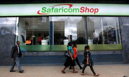 Pedestrians walk past a mobile phone care centre operated by Kenyan's telecom operator Safaricom in the central business district of Kenya's capital Nairobi