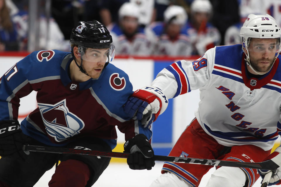 Colorado Avalanche center Tyson Jost, left, pursues the puck with New York Rangers forward Steven Fogarty during the second period of an NHL hockey game Wednesday, March 11, 2020, in Denver. (AP Photo/David Zalubowski)