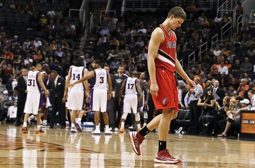 Portland Trail Blazers' Meyers Leonard, right, walks off the court dejectedly during the second half of an NBA basketball game against the Phoenix Suns, Wednesday, Nov. 21, 2012, in Phoenix. The Suns defeated the Trail Blazers 114-87. (AP Photo/Ross D. Franklin)