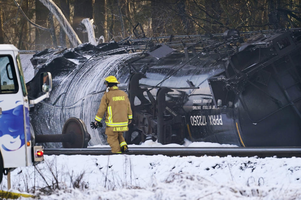 A firefighter walks past a derailed train car Tuesday, Dec. 22, 2020, in Custer, Wash. Officials say seven train cars carrying crude oil derailed and five caught fire north of Seattle and close to the Canadian border. Whatcom County officials said the derailment occurred in the downtown Custer area, where streets were closed and evacuations ordered during a large fire response. (AP Photo/Elaine Thompson)