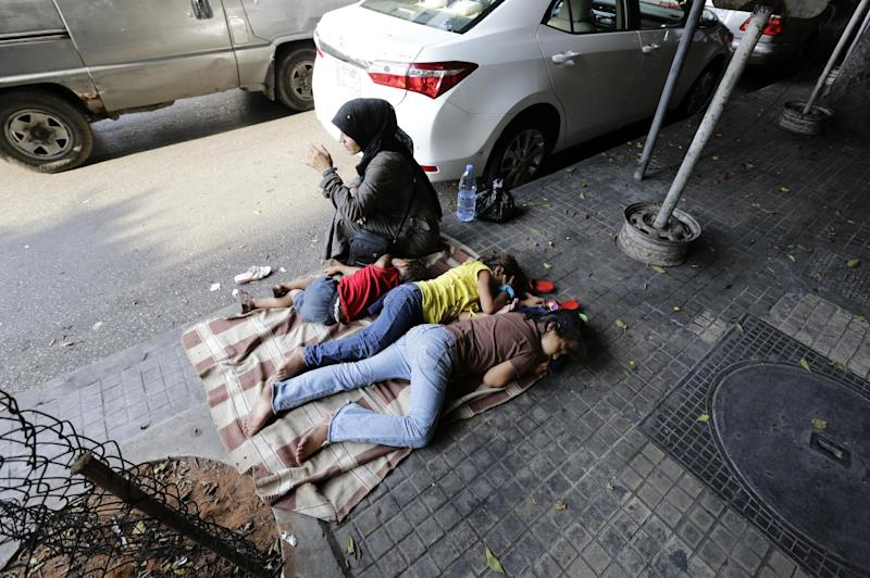 A Syrian woman sits next to her children sleeping on the street in Hamra Street in the Lebanese capital, Beirut, on August 29, 2014
