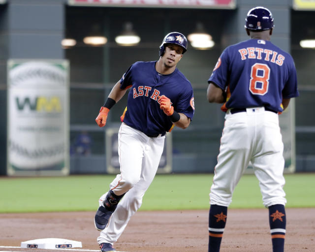 Houston Astros left fielder Michael Brantley, left, rounds third base as third base coach Gary Pettis, right, waits to celebrate Brantley's two-run home run against the Texas Rangers during the first inning of a baseball game Sunday, July 21, 2019, in Houston. (AP Photo/Michael Wyke)