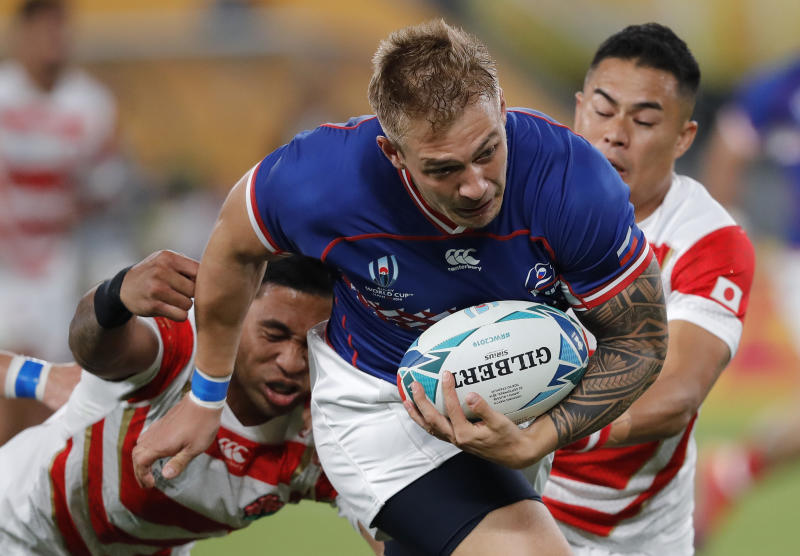 Russia's Kirill Golosnitskiy breaks through to score the opening try during the Rugby World Cup Pool A game at Tokyo Stadium between Russia and Japan in Tokyo, Japan, Friday, Sept. 20, 2019. (AP Photo/Christophe Ena)