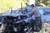 A law enforcement officer looks over a damaged vehicle following a rollover accident involving golfer Tiger Woods, Tuesday, Feb. 23, 2021, in the Rancho Palos Verdes suburb of Los Angeles. Woods suffered leg injuries in the one-car accident and was undergoing surgery, authorities and his manager said. (AP Photo/Ringo H.W. Chiu)