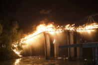 Flames engulf the Industry Bridge in Rome, early Sunday, Oct. 3, 2021. A blaze, possibly sparked by a gas canister explosion, destroyed part of an historic bridge spanning the Tiber River in Rome before firefighters extinguished the flames early Sunday. (Mauro Scrobogna/LaPresse via AP)