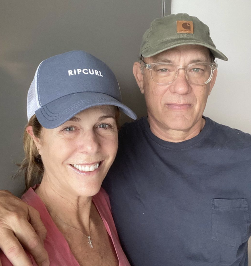 Tom Hanks and his wife, Rita Wilson, pose for a selfie while wearing hats in hospital