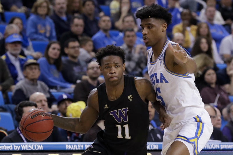 Washington guard Nahziah Carter, left, drives around UCLA guard Chris Smith during the second half of an NCAA college basketball game in Los Angeles, Saturday, Feb. 15, 2020. (AP Photo/Chris Carlson)