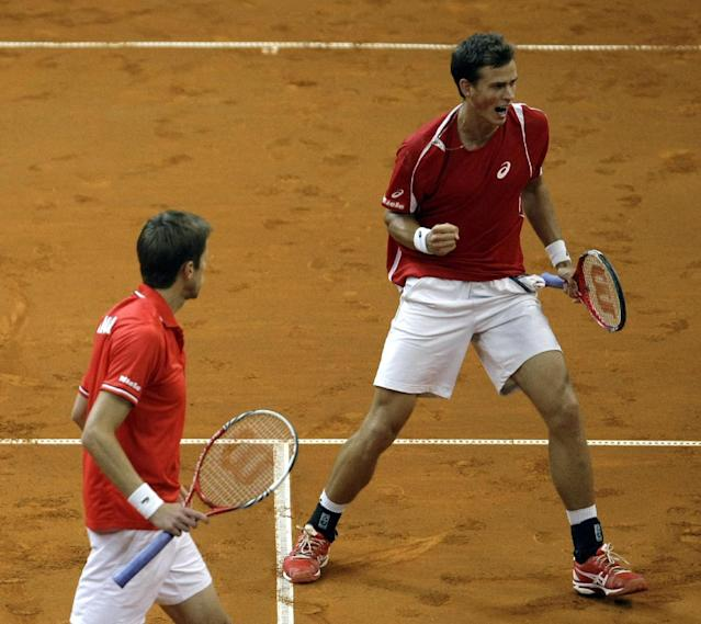 Canada's Vasek Pospisil, right, and partner Daniel Nestor celebrate winning a point against Serbia's Nenad Zimonjic and Ilija Bozoljac during their Davis Cup semifinals tennis doubles match in Belgrade, Serbia, Saturday, Sept. 14, 2013. (AP Photo/Marko Drobnjakovic)