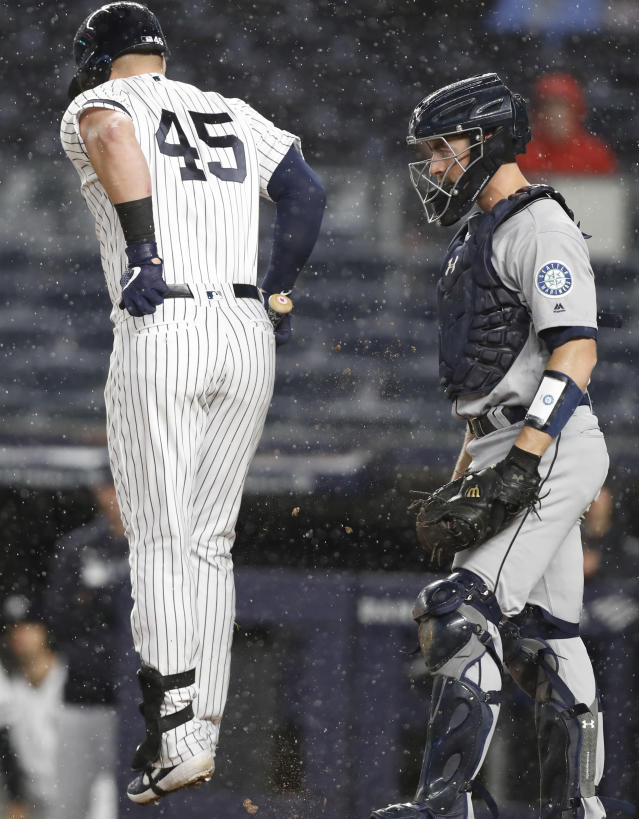 Seattle Mariners catcher Tom Murphy watches as New York Yankees Luke Voit (45) leaps after he was hit on the foot by a pitch during the sixth inning of a baseball game, Tuesday, May 7, 2019, in New York. (AP Photo/Kathy Willens)