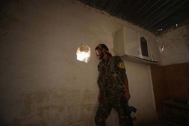 <p>A Syrian Democratic Forces (SDF) fighter takes a position inside a building in the al-Mishlab district at Raqqa's southeastern outskirts, Syria June 7, 2017. (Photo: Rodi Said/Reuters) </p>