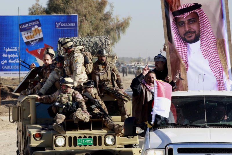 Security forces and mourners escort the coffin of Ifan Saadoun al-Issawi, seen in the poster, during his funeral in Fallujah, 40 miles (65 kilometers) west of Baghdad, Iraq, Wednesday, Jan. 16, 2013. The Sunni-backed Iraqiya bloc lawmaker was assassinated by a suicide bomber in Fallujah on Tuesday. (AP Photo/ Hadi Mizban)