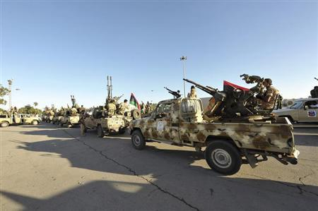 Demonstrators protest against armed militias as they welcome the arrival of the Libyan army in Benghazi