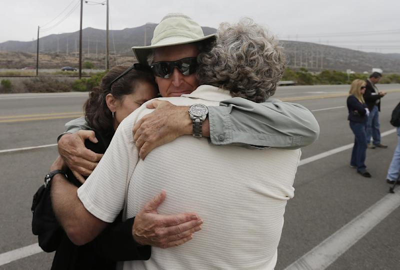 Gary Headrick, right, hugs Steve Netherby, center, and his wife Laurie Headrick, left, before a news conference by opponents of the San Onofre nuclear power plant near the entrance to the plant Friday, June 7, 2013, in San Onofre, Calif. The troubled power plant on the California coast is closing after an epic 16-month battle over whether the twin reactors could be safely restarted with millions of people living nearby, officials announced Friday. (AP Photo/Gregory Bull)