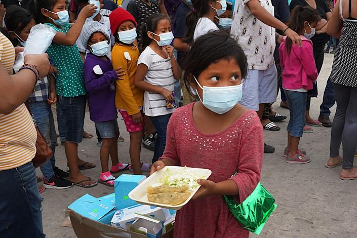 A child holds a plate of food while other children and adults are lined up nearby