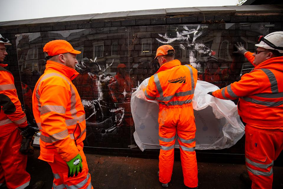 Workmen use perspex sheeting to protect a new Banksy artwork in Birmingham's Jewellery Quarter after it was vandalised days after it first appeared. The mural depicts two reindeer painted onto a brick wall appearing to pull along a bench.