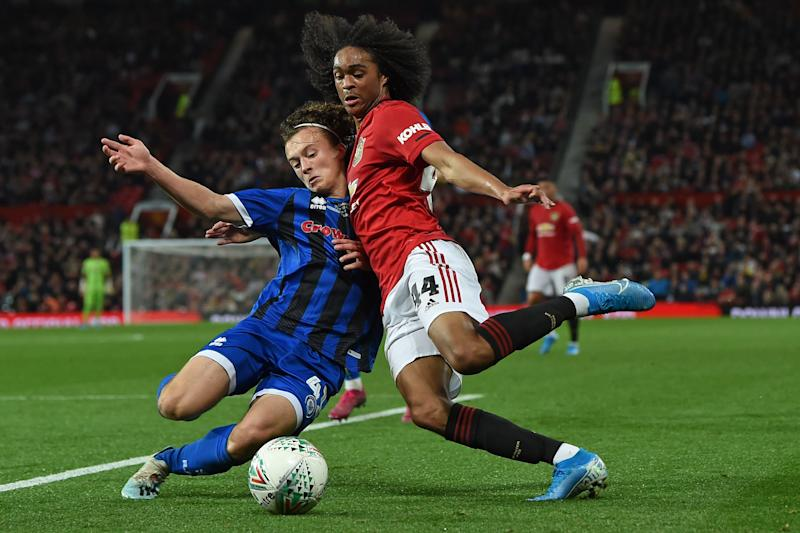 TOPSHOT - Rochdale's English defender Luke Matheson (L) vies with Manchester United's Dutch midfielder Tahith Chong (R) during the English League Cup third round football match between Manchester United and Rochdale at Old Trafford in Manchester, north-west England on September 25, 2019. (Photo by Paul ELLIS / AFP) / RESTRICTED TO EDITORIAL USE. No use with unauthorized audio, video, data, fixture lists, club/league logos or 'live' services. Online in-match use limited to 120 images. An additional 40 images may be used in extra time. No video emulation. Social media in-match use limited to 120 images. An additional 40 images may be used in extra time. No use in betting publications, games or single club/league/player publications. / (Photo credit should read PAUL ELLIS/AFP/Getty Images)