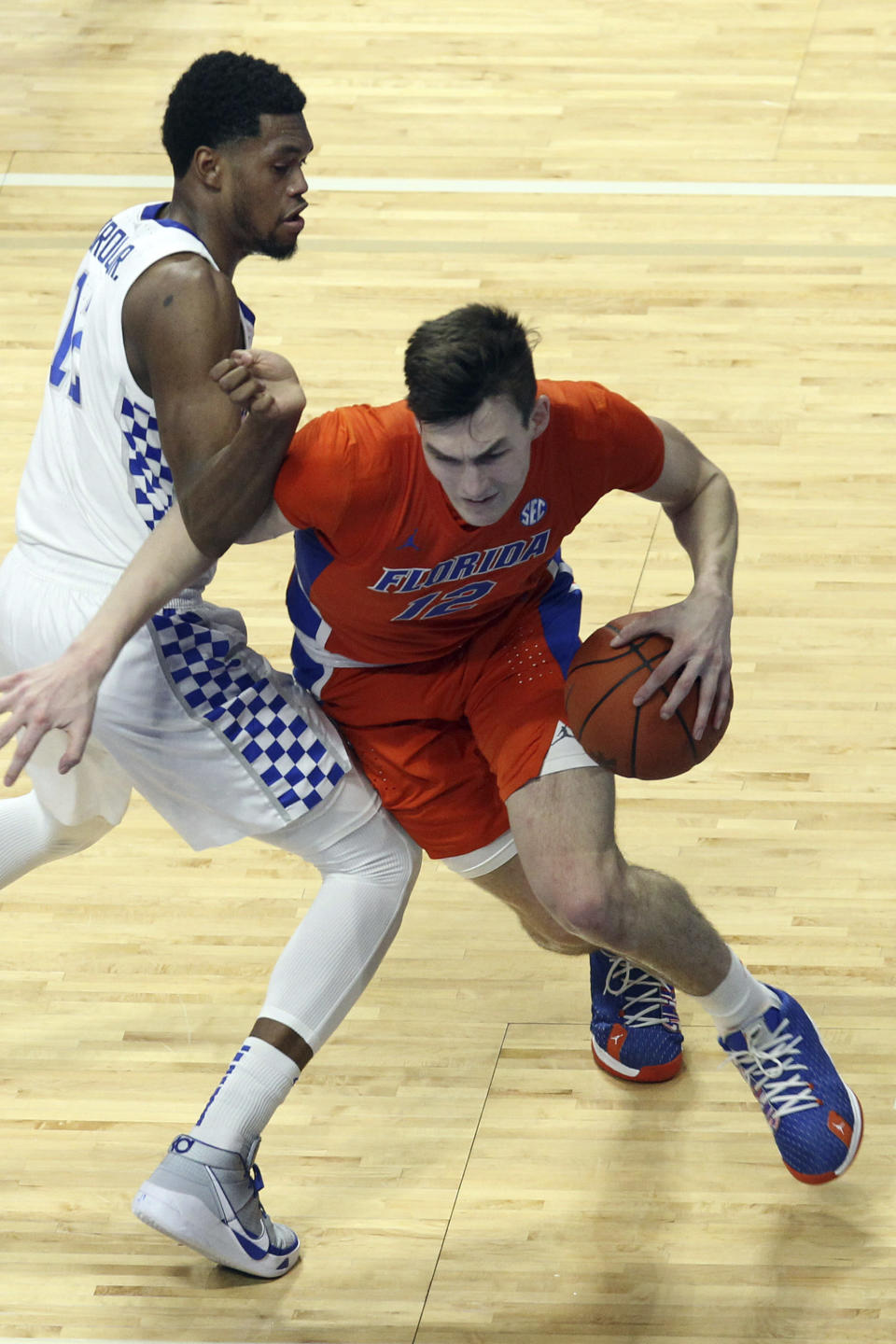 Florida's Colin Castleton, right, drives while defended by Kentucky's Keion Brooks Jr. during the first half of an NCAA college basketball game in Lexington, Ky., Saturday, Feb. 27, 2021. (AP Photo/James Crisp)