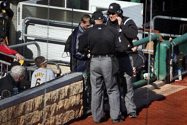 First base umpire Bob Davidson, right, and home plate umpire John Hirschbeck, center, talk over headsets as a pickoff safe call at first base is reviewed in the tenth inning of an opening day baseball game against the Chicago Cubs on Monday, March 31, 2014, in Pittsburgh. The safe call was overturned and Cubs' Emilio Bonifacio was ruled out. The Pirates won 1-0 in ten innings. (AP Photo/Gene J. Puskar)