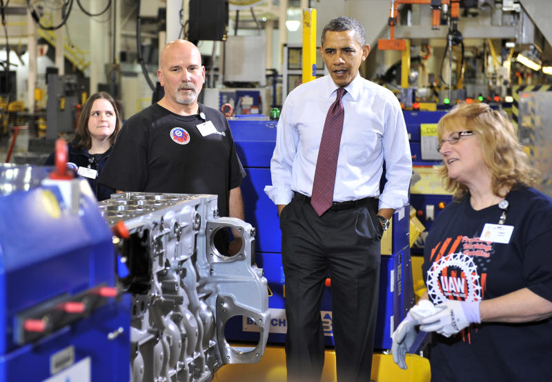 President Barack Obama listens as Cindy Burtis, right, talks about the head line with Tom Percha, left, at far left is Brandy Reynolds, at Detroit Diesel in Redford, Mich. on Monday, Dec. 10, 2012. Daimler AG plans to announce $100 million investment into the facility at Detroit Diesel. (AP Photo/The Detroit News, Robin Buckson, Pool)