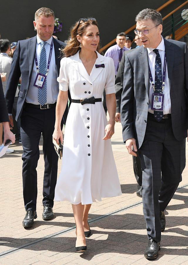 """Kate has had a helping hand in her bold new look. Natasha Archer, the royal's longtime assistant and stylist, recently returned to work following her <a href=""""https://people.com/royals/kate-middleton-stylist-natasha-archer-royals-photographer-chris-jackson-welcome-baby-boy/"""" rel=""""nofollow noopener"""" target=""""_blank"""" data-ylk=""""slk:maternity leave"""" class=""""link rapid-noclick-resp"""">maternity leave</a>. <a href=""""https://people.com/royals/kate-middleton-surprises-wimbledon-fans-and-not-in-the-royal-box/"""" rel=""""nofollow noopener"""" target=""""_blank"""" data-ylk=""""slk:Kate took in a few matches at Wimbledon"""" class=""""link rapid-noclick-resp"""">Kate took in a few matches at Wimbledon</a> wearing a white midi dress by Suzannah featuring black buttons down the front. She accessorized with an Alexander McQueen belt, chic sunglasses and her signature blowout."""