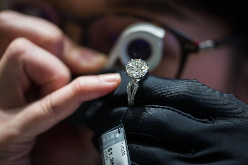 An employee inspects a diamond ring inside a Chow Tai Fook Jewellery Group Ltd. store in the Central district of Hong Kong, China, on Friday, Jan. 20, 2017. Chow Tai Fook, the world's largest jewelry chain, last year launched the first of a line of mainland shops selling lower-priced jewelry, with average prices of 2,000 yuan ($291), about a third the prices at its flagship stores. Photographer: Billy H.C. Kwok/Bloomberg via Getty Images