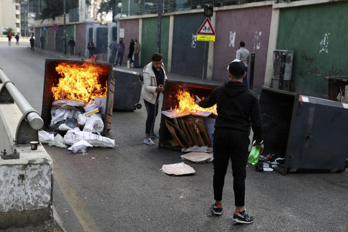 Protesters burn garbage containers to block a road in Beirut, Lebanon, Monday, March 8, 2021. The dayslong protests intensified Monday amid a crash in the local currency, increase of consumer goods prices and political bickering between rival groups that has delayed the formation of a new government. (AP Photo/Bilal Hussein)