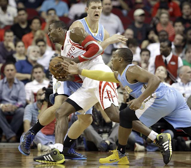 Houston Rockets' Dwight Howard, left, goes to the basket between Denver Nuggets Randy Foye, right, and Timofey Mozgov in the first half of an NBA basketball game Saturday, Nov. 16, 2013, in Houston. (AP Photo/Pat Sullivan)