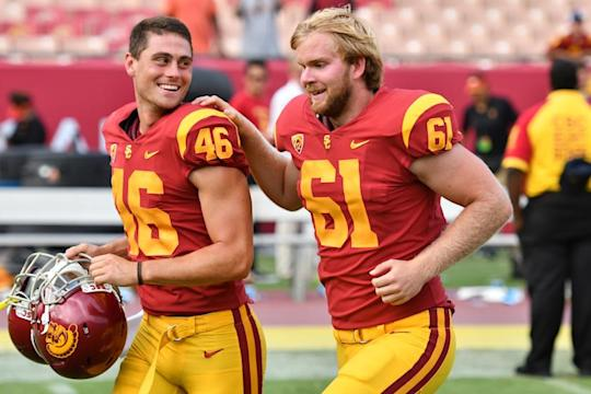 USC's blind long snapper, Jake Olson (R), got on the field Saturday, but coach Clay Helton made him earn the appearance like any other player on his team. (Getty)