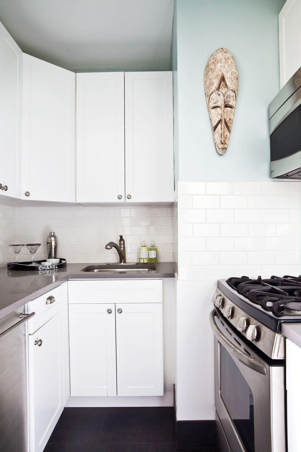"<p>When space is limited, you have to find creative ways to add a little fancy flair. Here, interior designer <a href=""http://www.dcdny.com/"" rel=""nofollow noopener"" target=""_blank"" data-ylk=""slk:Danielle Colding"" class=""link rapid-noclick-resp"">Danielle Colding</a> added a powder blue accent wall and a sculpture but kept everything else glistening and white. The Chanel tray on the counter for serving also doubles as decor. </p>"