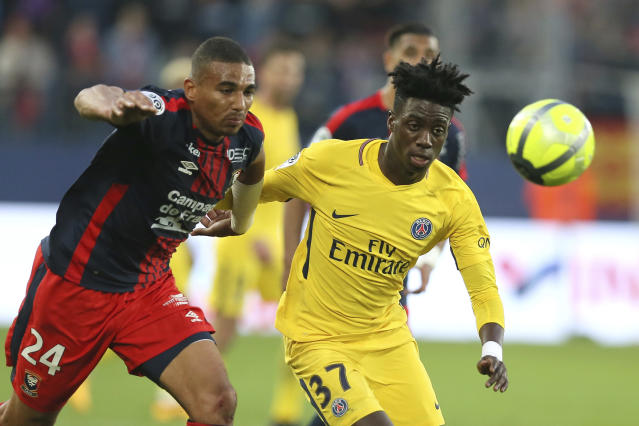 Timothy Weah of Paris Saint Germain challenges for the ball with Alexander Djiku of Caen during their League One soccer match at the Michel d'Ornano stadium in Caen, western France, Saturday, May 19, 2018. (AP Photo/David Vincent)