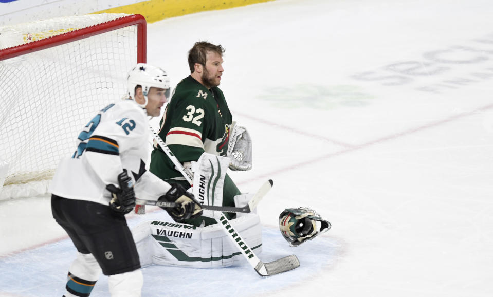 Minnesota Wild goalie Alex Stalock loses in mask as San Jose Sharks' Patrick Marieau, left, looks for the pass in the third period of an NHL hockey game, Saturday, Feb. 15, 2020, in St. Paul, Minn. San Jose won 2-0.(AP Photo/Tom Olmscheid)