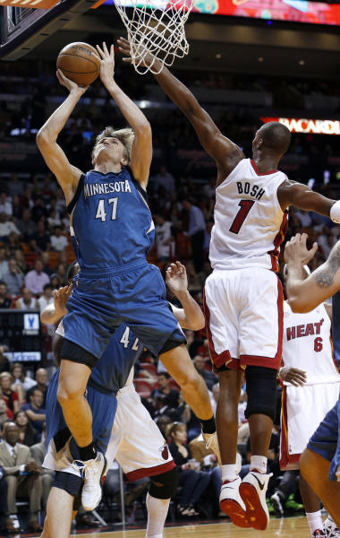 Minnesota Timberwolves' Andrei Kirilenko (47) goes to the basket as Miami Heat's Chris Bosh (1) defends during the first half of an NBA basketball game Tuesday, Dec. 18, 2012, in Miami. (AP Photo/Alan Diaz)