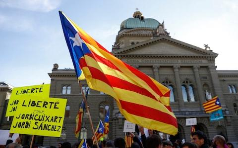 The Catalan flag is waved next to the Bundeshaus, the Swiss parliament building, during a demonstration in support of Catalonia, in Bern, Switzerland. - Credit: Peter Klaunzer/Keystone